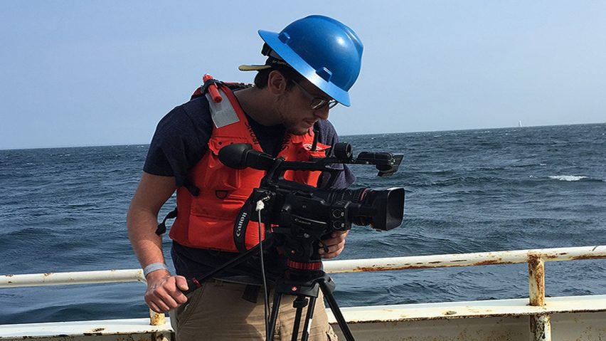 Kyle Sidlik shoots video with a large studio camera on the deck of R/V Endeavor.
